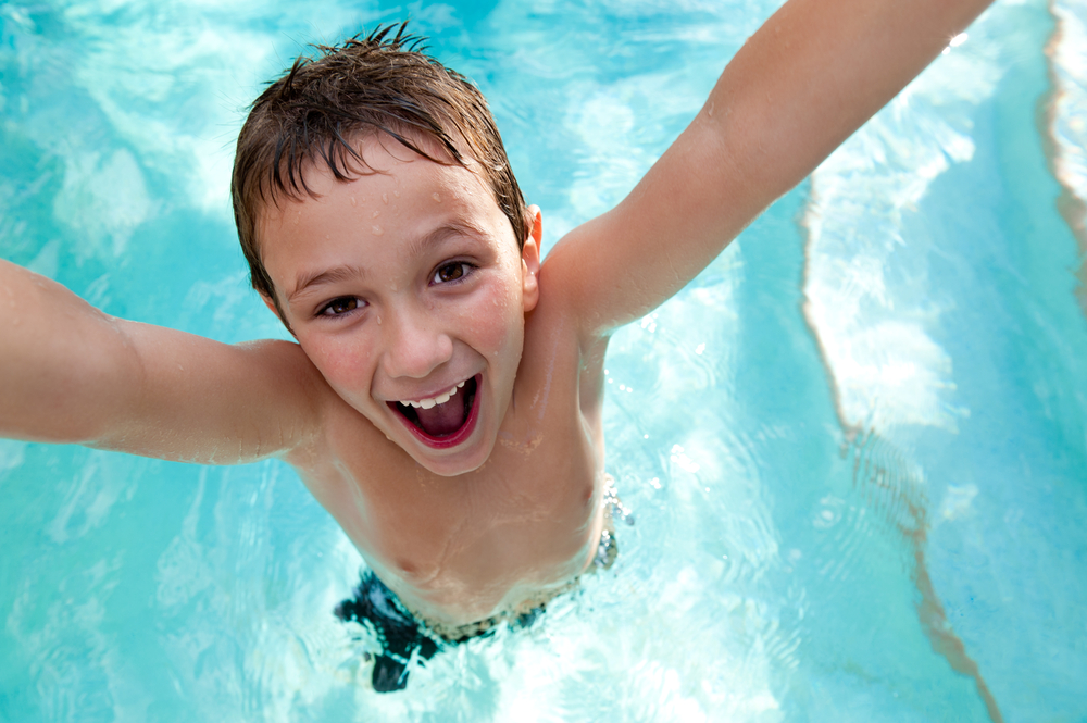 young boy smiling with arms up in swimming pool at Mountain Melodies